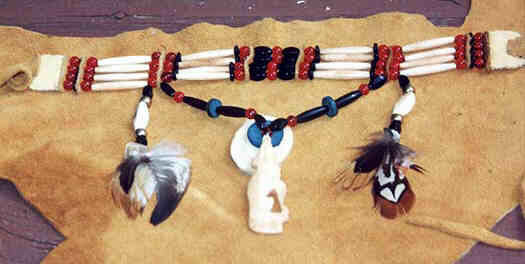 Choker, necklace presented on deerskin.  Four leather strands carry beads symmetrically arranged from the center outward:  Central red bead, black oval bead, leather separator, red bead, black washer,  long white bi-conic buffalo horn bead, black washer, red bead, leather separator,  red bead, long white bi-conic buffalo horn bead, red bead, leather separator, red  bead, and white beaded section for closing.  Hanger string extending downwards from leather separators between the two red  beads between the white buffalo horn beads, symmetrically from the center out- and  upward: turquoise blue bead, black oval bead, red round bead, long black oval bead,  turquoise disk, long black oval bead, red bead, oval black bead. Hanger at the  middle at blue bead showing frontal: blue disk - twice the size of the blue disk in  hanger string - on upper half of twice as big white bone or horn disk. Sitting Wolf  of carved white bone howls into the blue disc center as to the moon.  Hanger left and right of the hanger string - extending from between the red bead  and the white bone: black oval bead, metallic bead, thick white horn oval bead,  metallic bead, black oval bead, various beautifully colored small feathers.