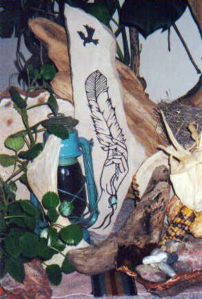 Long irregularly shaped flat sandstone,  leaning against driftwood, surrounded by  smaller driftwood, stones, dark spackled  yellow maize and kerosene lamp.   Graph carved into the slab shows a slender  female hand holding up a dark tipped eagle  feather to an Eagle shade soaring above  looking down. The shaft of the feather  decorated with dangling strings.