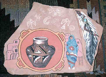 Irregular hexagonal flat sandstone painted  with Native Mexican motives in Native style in pastel colors.  Dominating from central left is a round bordered circle with  diagonal markings of the Four Directions. In it a painting of  a Mexican Native Jug, with zig-zag and other decorative motives.  Left of the mandala four parts of a rising Pueblo with a ladder  leading to the entries. Right of the mandala a woman stands in  front of a Pueblo with a ladder and steep stairway. All but her  face and white moccasins are wrapped in a beautifully decorated  light-blue blanket.  Above the mandala six white archaic Animal  Spirit symbols - Eagle, Wolf, Buffalo, Cariboo, Whale and Hawk –  and two round dotted motives.   To the right of this area a lower triangular level. One tattered  Eagle feather fills the space. Its tip points downwards, fitting  snug into the natural form of the stone. At the top a leather  string wraps around the feather's hollow shaft. An inlaid  turquoise appears threaded onto the leather string.  The stone leans against a handwoven carped showing similar  motives and colors as the jug in the mandala.