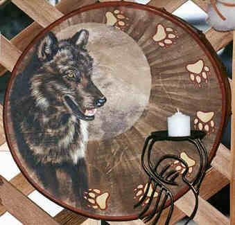 Round drum painted.  A dark colored Wolf stands left in front of  a radiating halo around its head and breast.  Wolf looks East with pointed attentive ears  and open mouth, showing its white teeth.  Seven wolf paw- or footprints run along the  drum border from center top to left lower left.  Each heart shaped metacarpal pad with four  digital pads and claw imprints beneath.